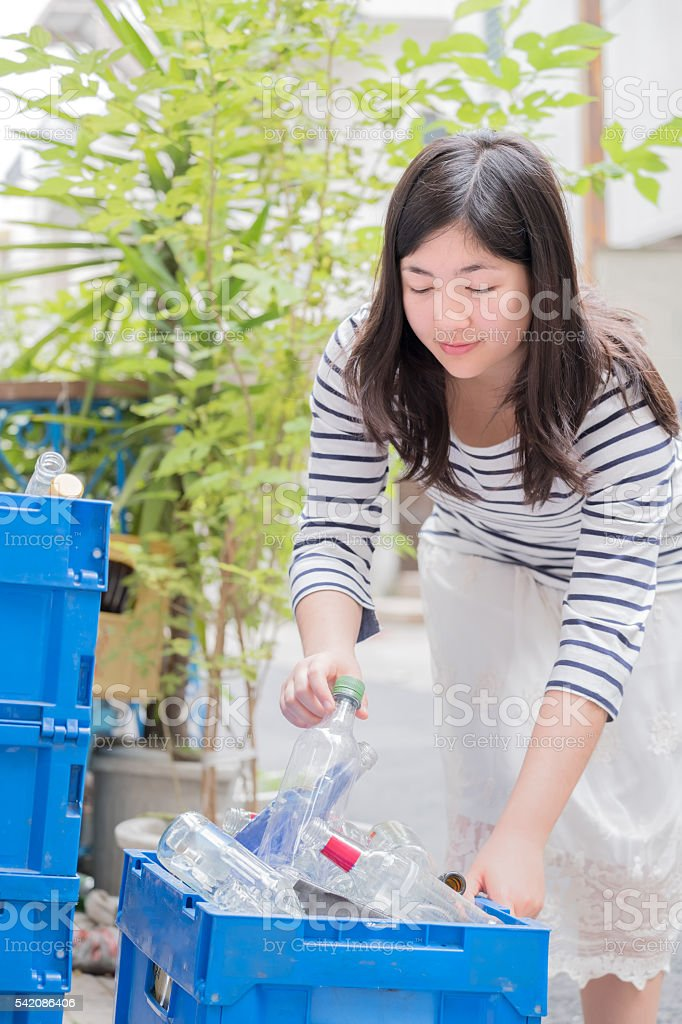 Smiling Young Woman Recycling Glass Bottles in Alley, Tokyo, Japan stock photo