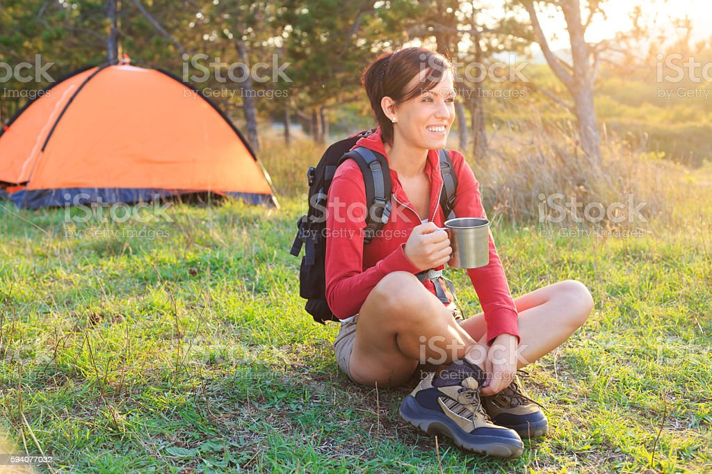 Smiling young woman resting in front of a tent stock photo