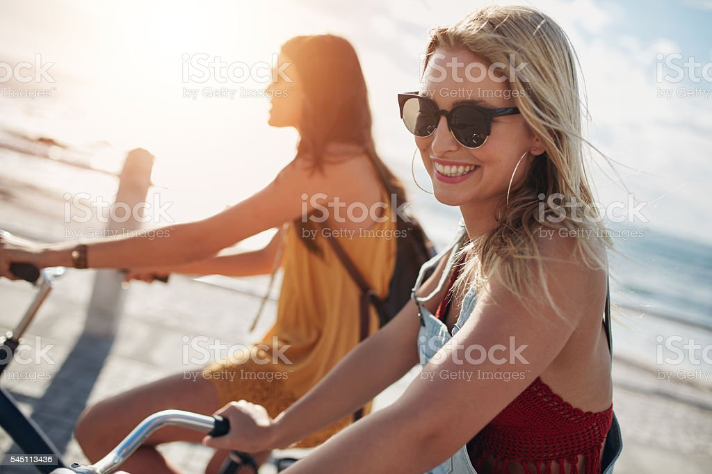 Smiling young woman riding bicycle with her friend stock photo