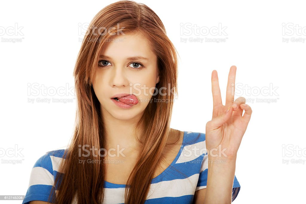Smiling young woman showing the victory sign stock photo