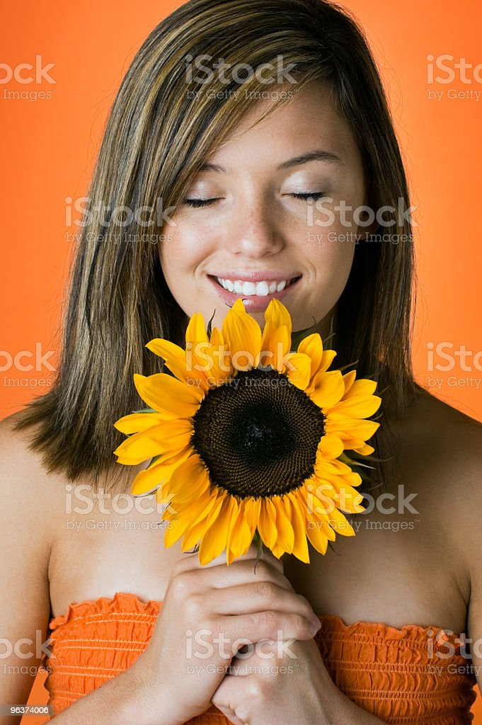 Smiling Young Woman Smelling Sunflower stock photo