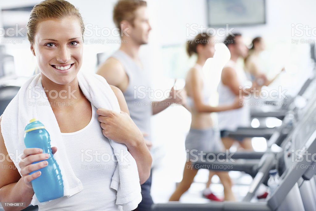 Smiling young woman standing beside treadmill royalty-free stock photo