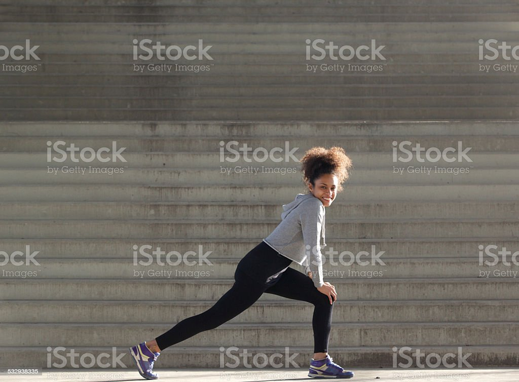Smiling young woman stretching leg muscles stock photo