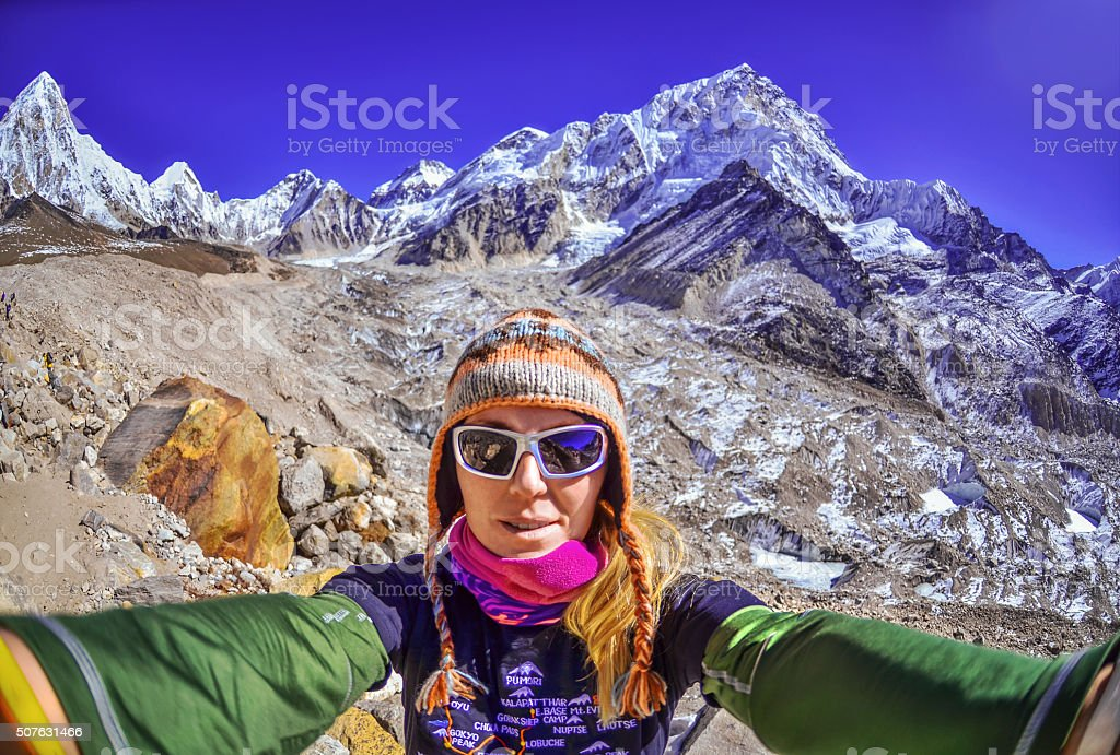 Smiling young woman takes a selfie  on mountain peak stock photo