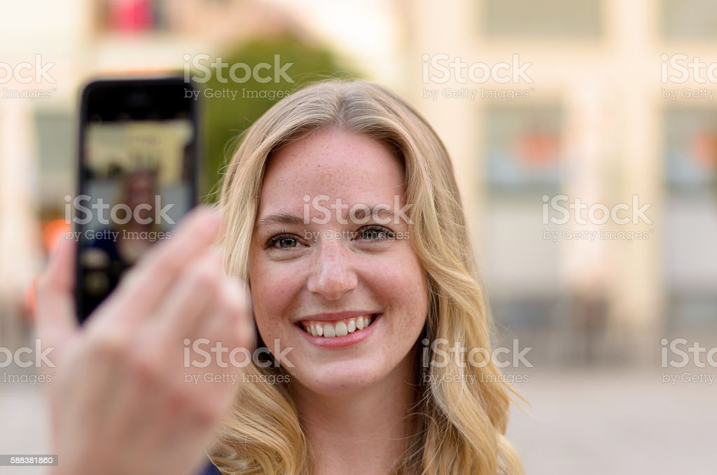 Smiling young woman taking her selfie stock photo
