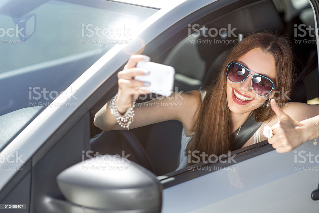 Smiling young woman taking selfie picture in the car stock photo
