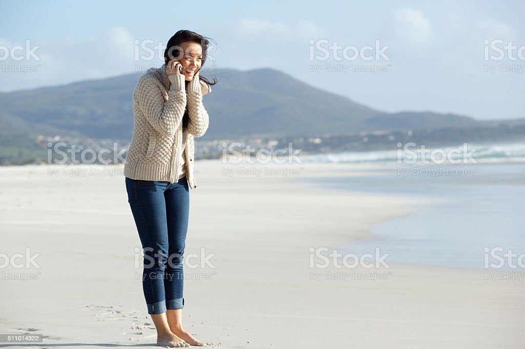Smiling young woman talking on cell phone at the beach stock photo