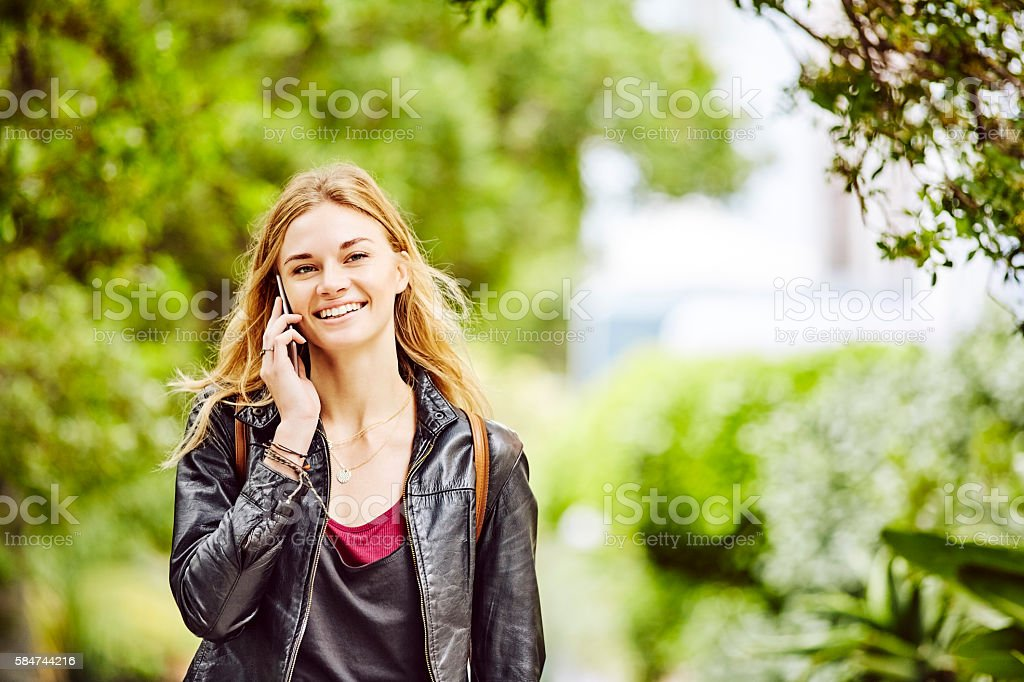 Smiling young woman talking on smart phone on leafy street stock photo