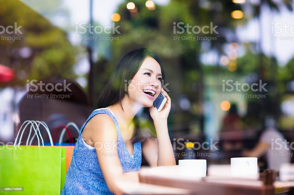 smiling young woman talking on the phone in cafe shop stock photo