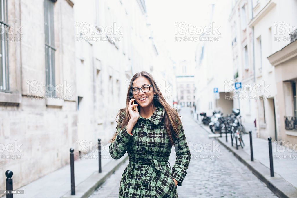 Smiling young woman talking on the phone outside stock photo