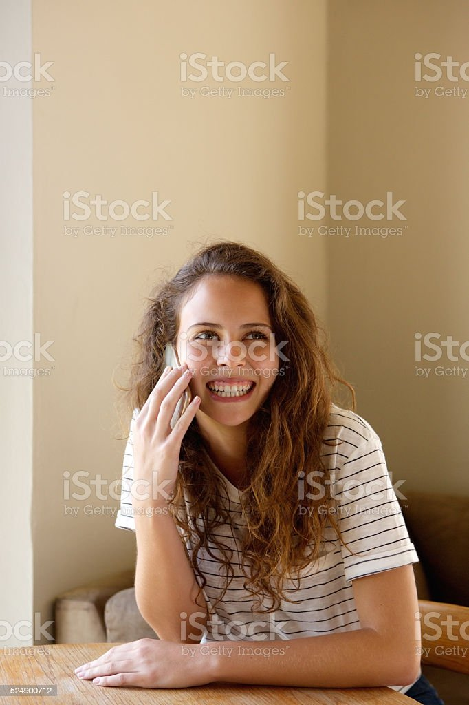 Smiling young woman talking with cell phone at cafe stock photo