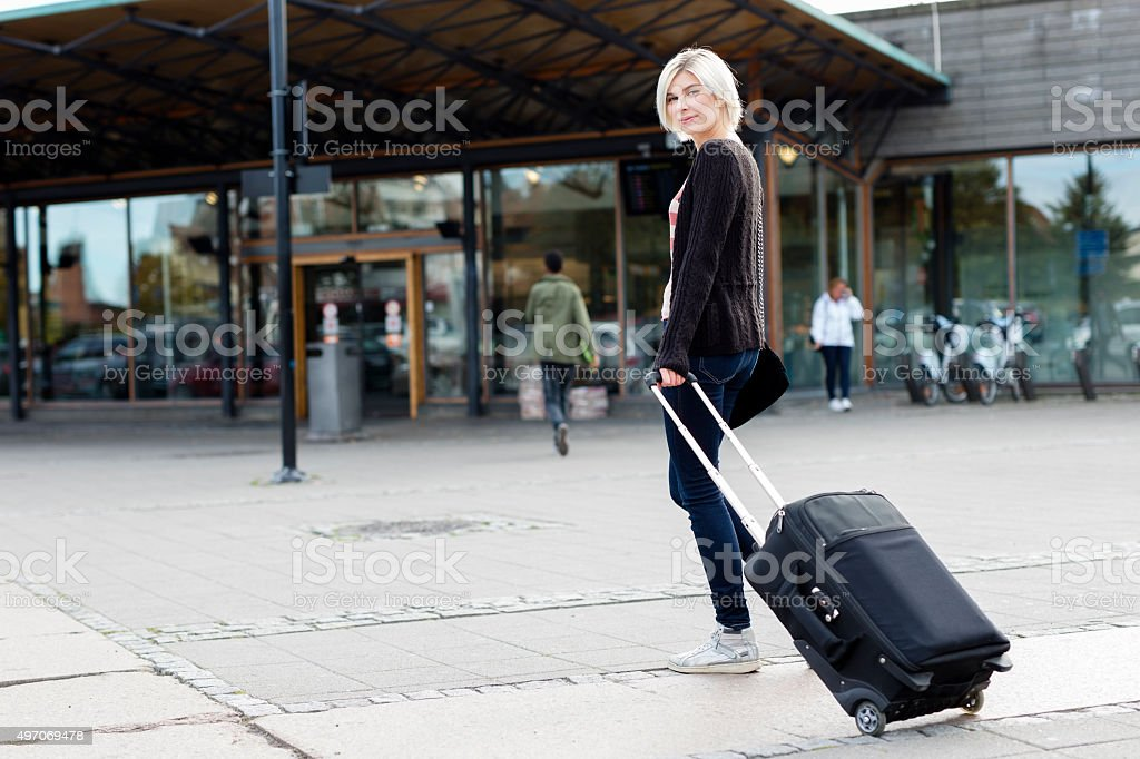 Smiling young woman traveling with a wheeled suitcase stock photo