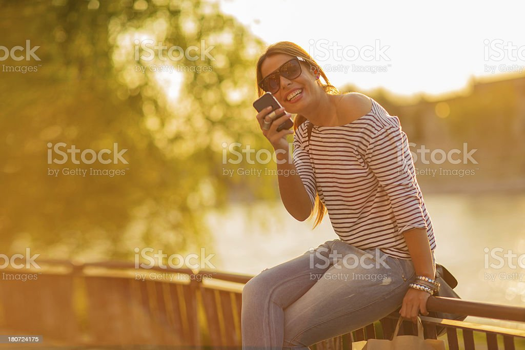 Smiling young woman using a smartphone outdoors royalty-free stock photo