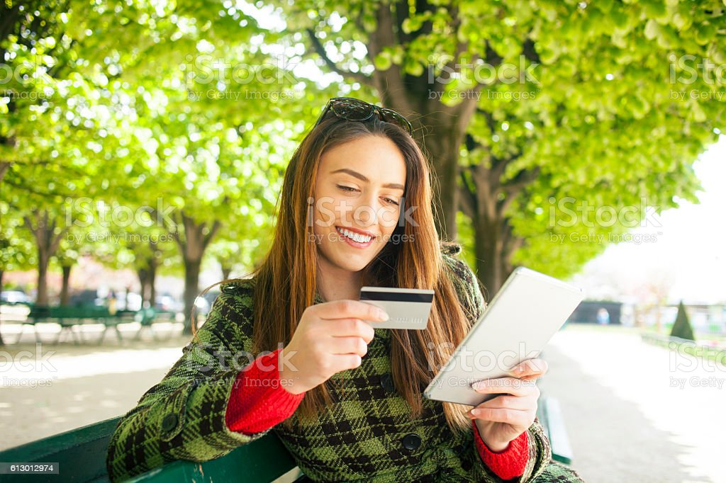 Smiling young woman using credit card for online shopping stock photo
