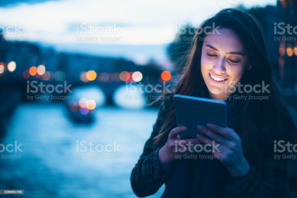 Smiling young woman using digital tablet on bridge by night stock photo