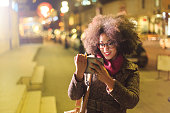 Smiling young woman using digital tablet on street at night