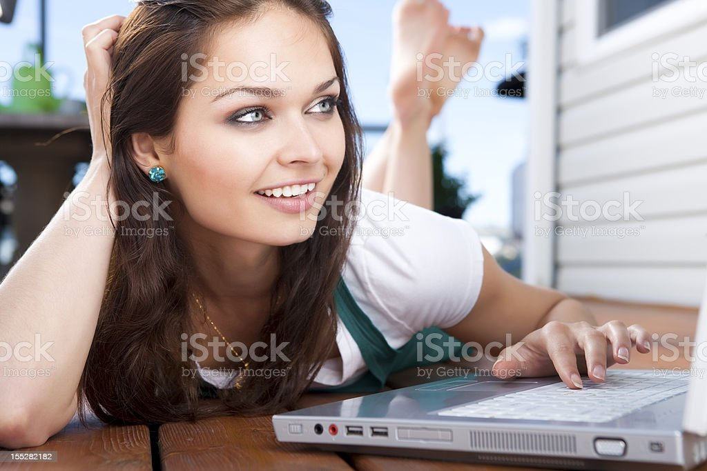 Smiling young woman using laptop on deck royalty-free stock photo