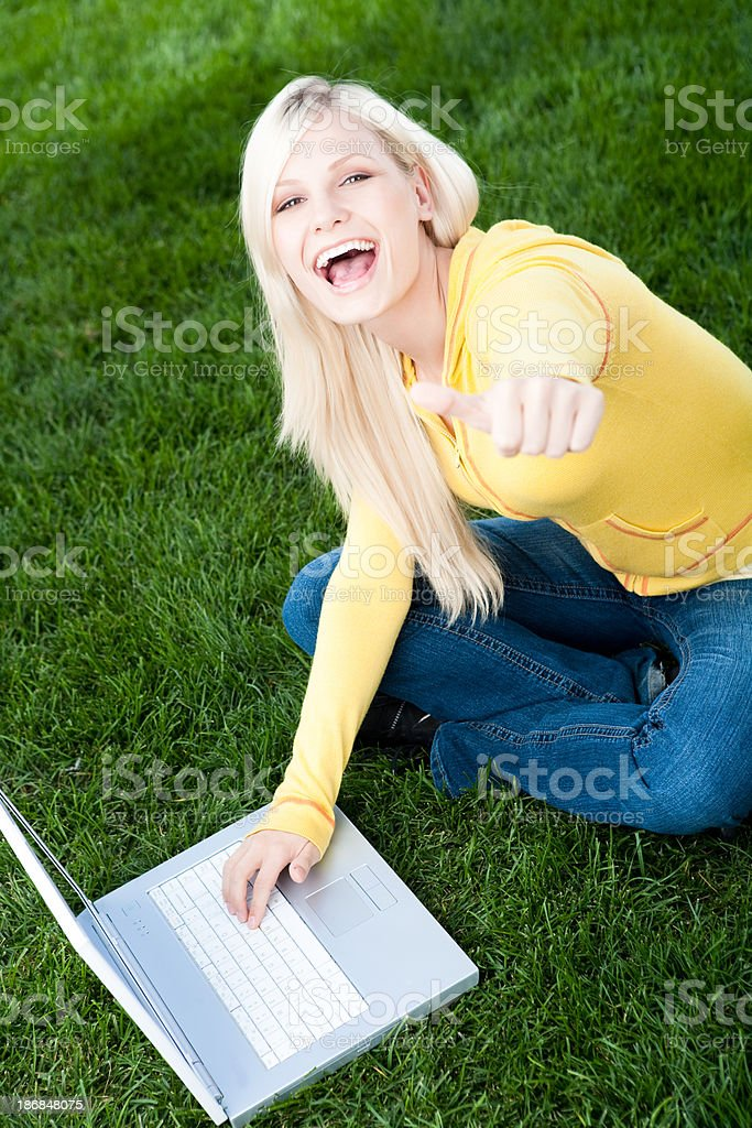 Smiling young woman using laptop royalty-free stock photo