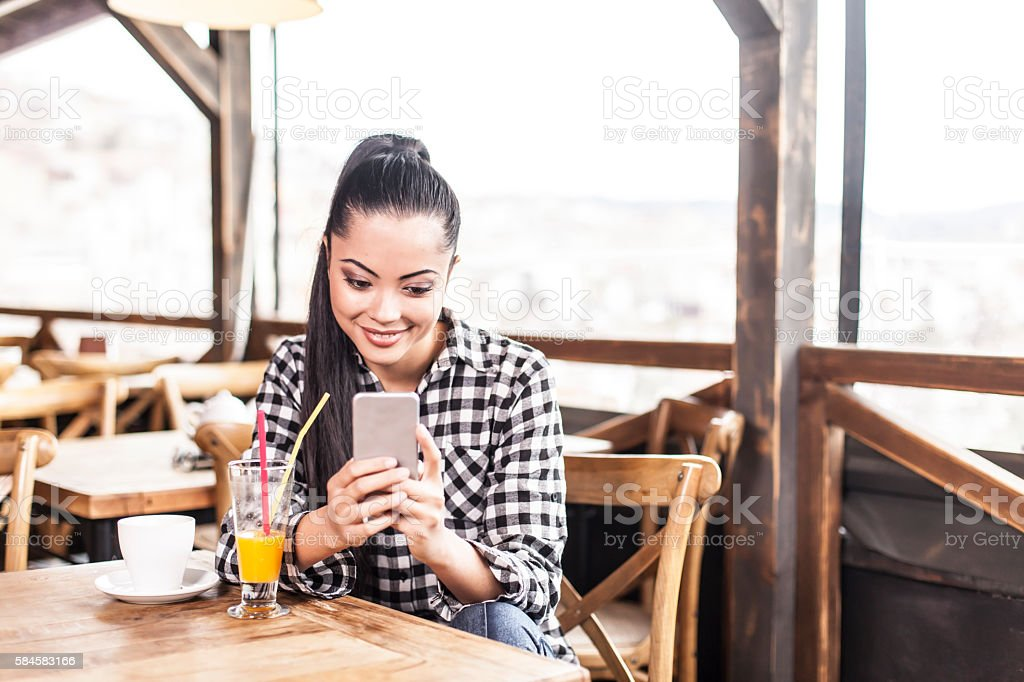 Smiling young woman using phone at coffee shop stock photo