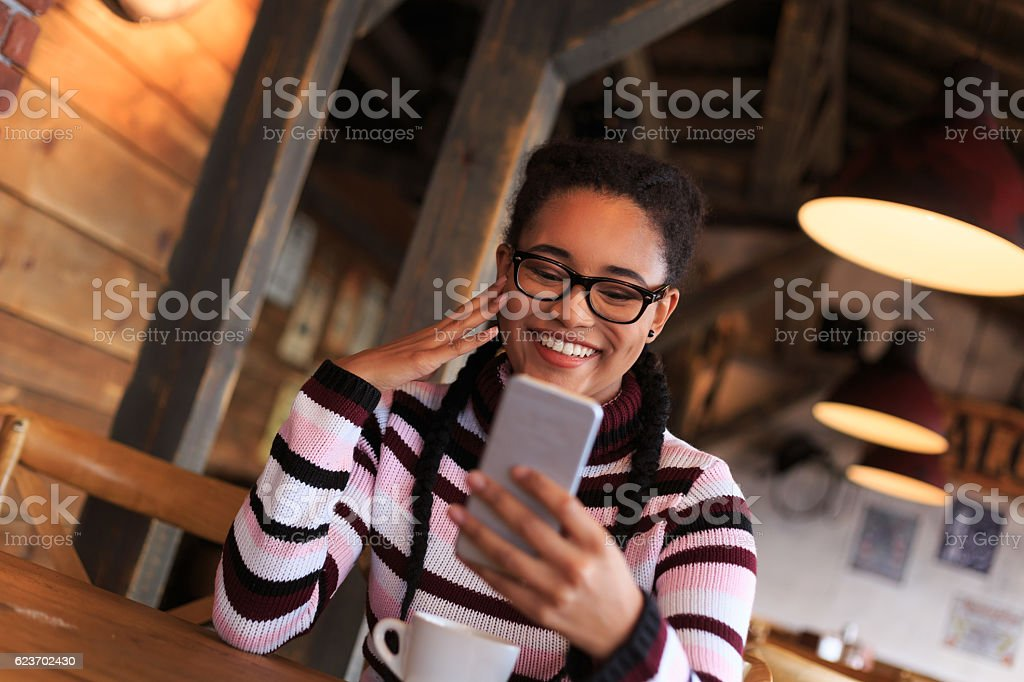 Smiling young woman using smart phone in a bar stock photo