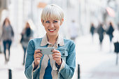 Smiling young woman using smart phone on street