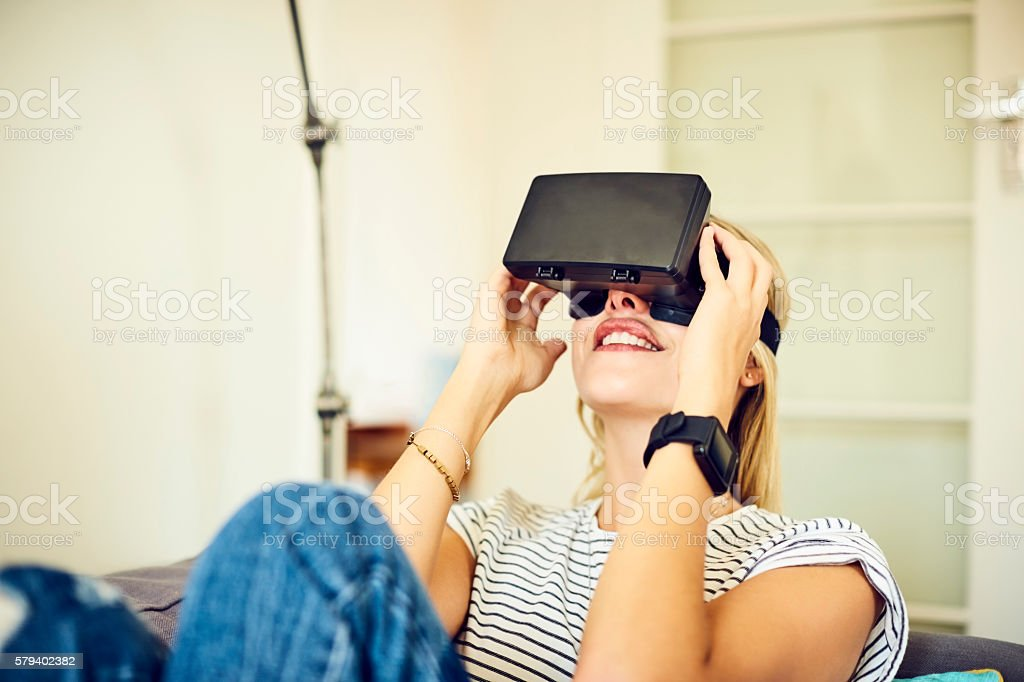 Smiling young woman using VR headset at home on couch stock photo