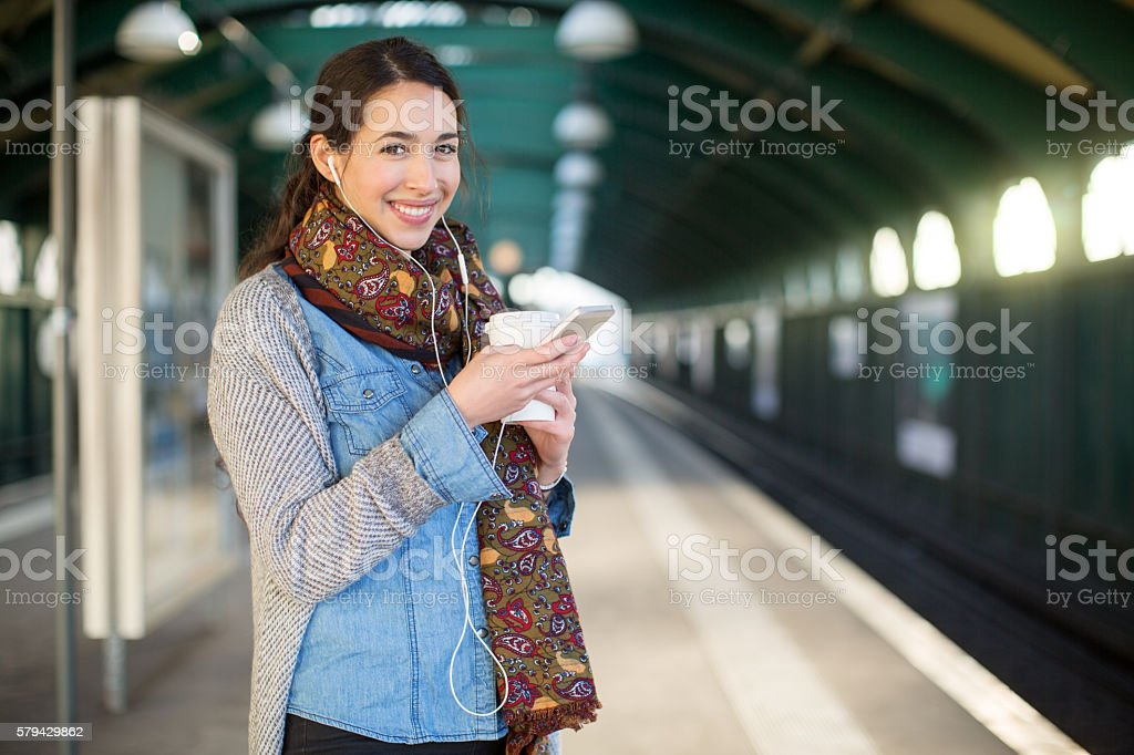 Smiling young woman waiting at subway station stock photo