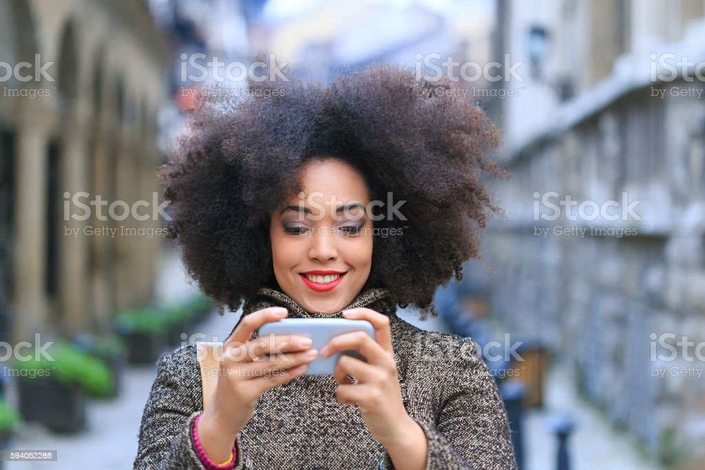 Smiling young woman walking on street and making selfie stock photo