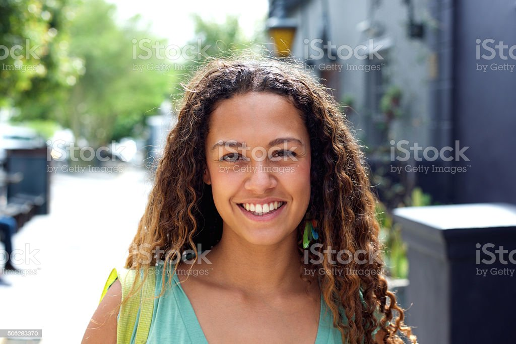 Smiling young woman walking outdoors in the city stock photo
