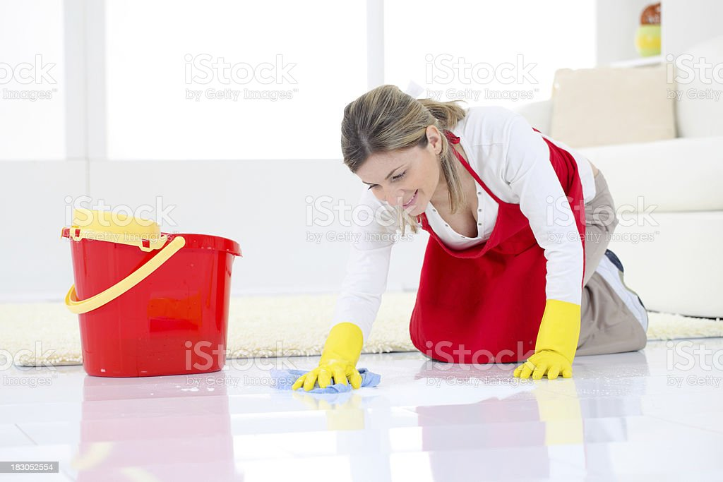 Smiling young woman washing floor at the home. stock photo