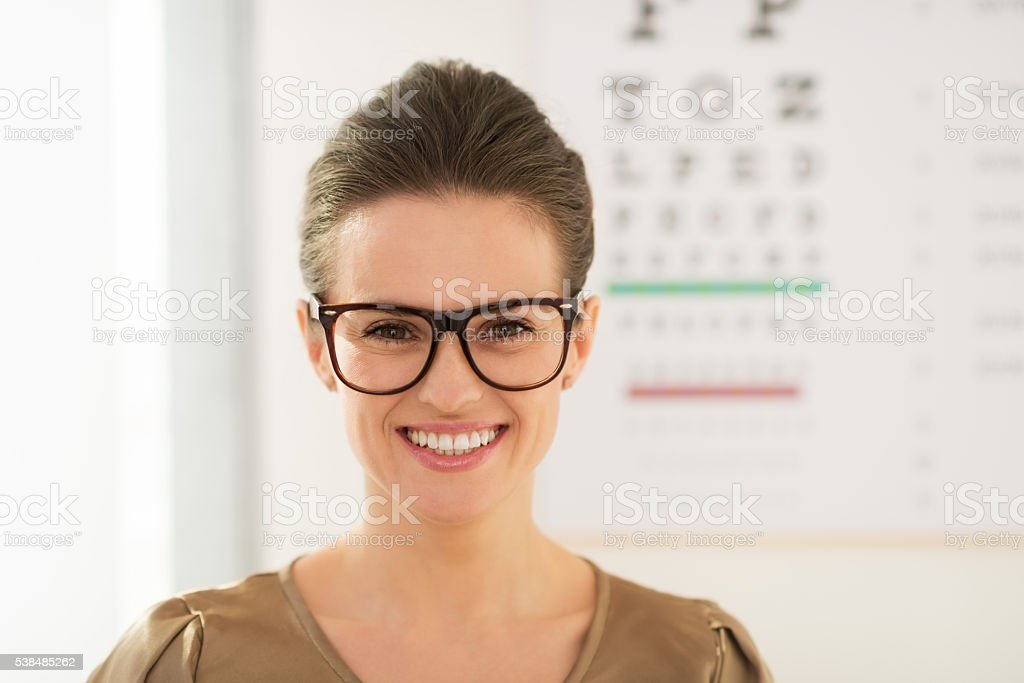 Smiling young woman wearing eyeglasses in front of Snellen chart stock photo