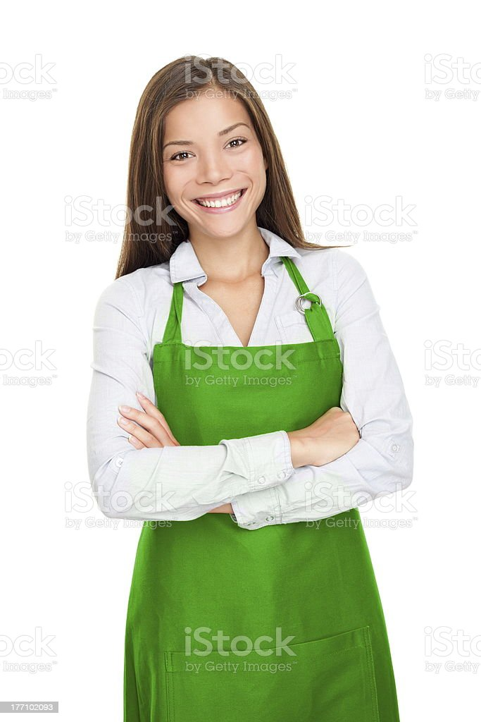 Smiling young woman wearing green apron stock photo