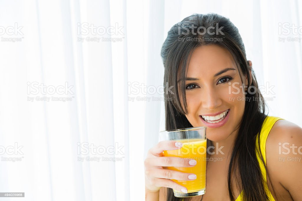 Smiling young woman with a glass of orange juice stock photo