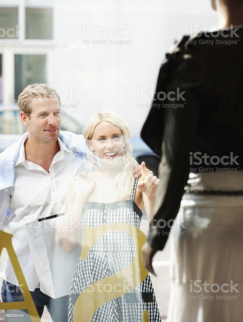 Smiling young woman with a man pointing at window display royalty-free stock photo