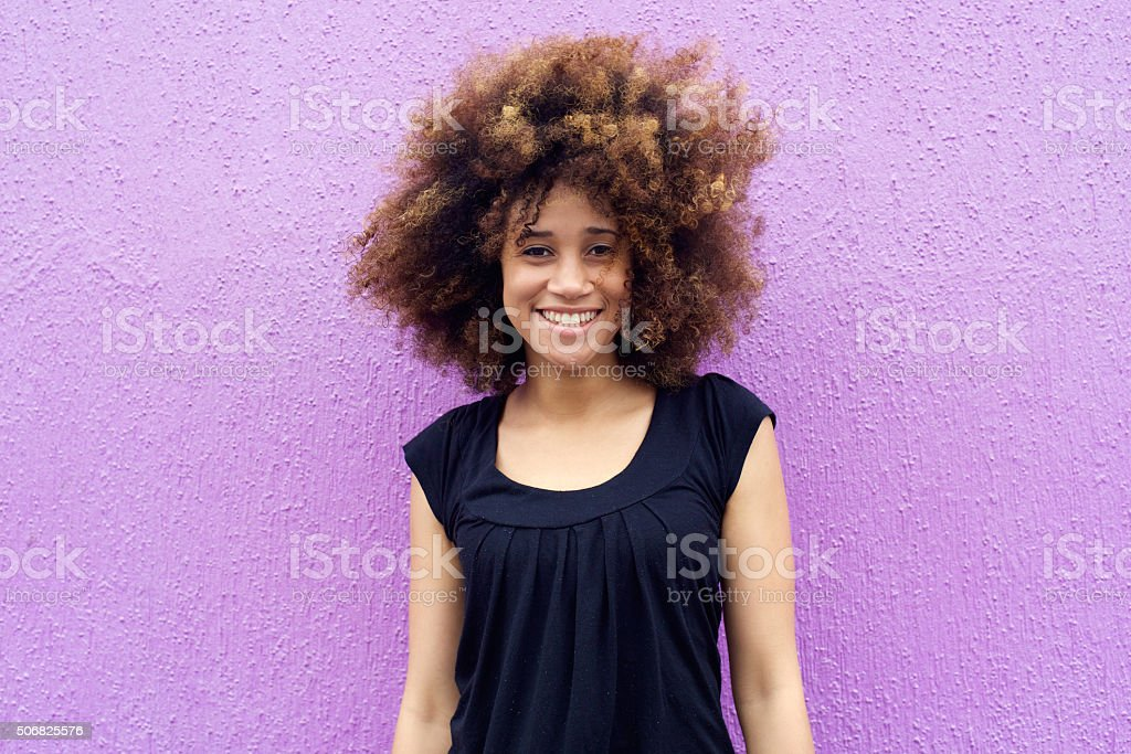 Smiling young woman with afro against purple background stock photo