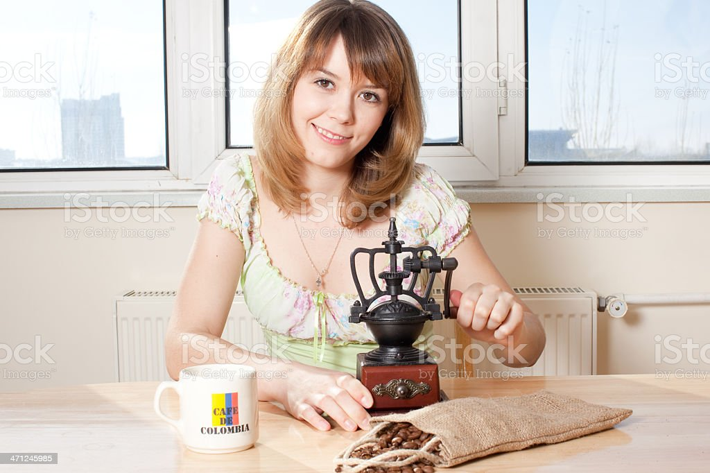 Smiling Young Woman with Coffee Grinder stock photo