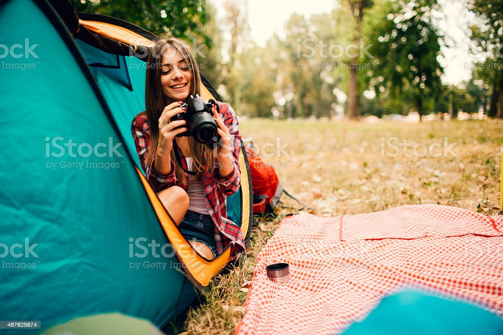 Smiling Young Woman With Digital Camera Camping. stock photo