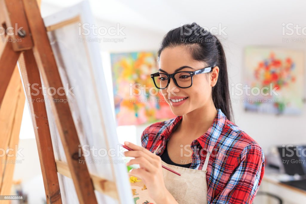 Smiling young woman with eyeglasses drawing stock photo