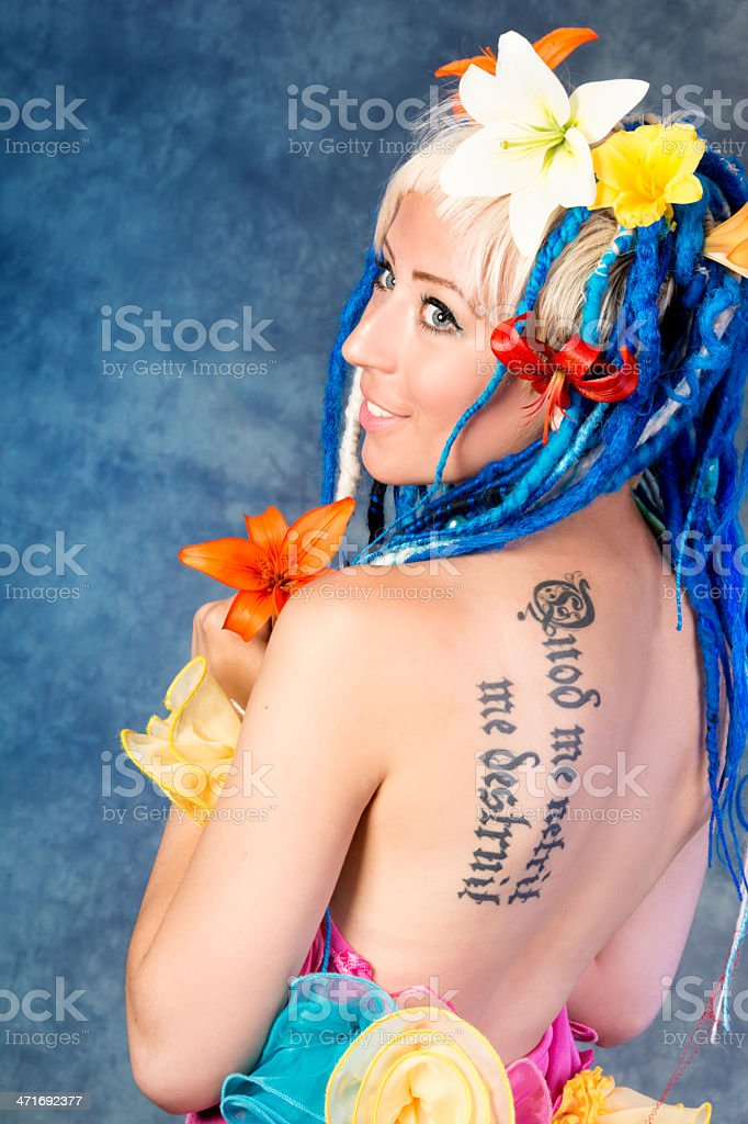 Smiling young woman with flowers in hair and tattoo. royalty-free stock photo