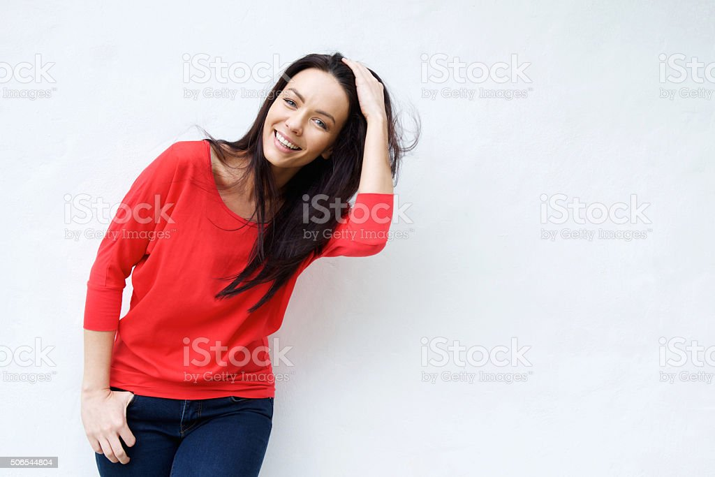Smiling young woman with hand in hair stock photo