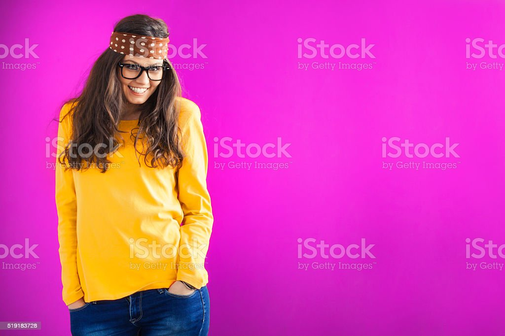 Smiling young woman with headband on purple background stock photo