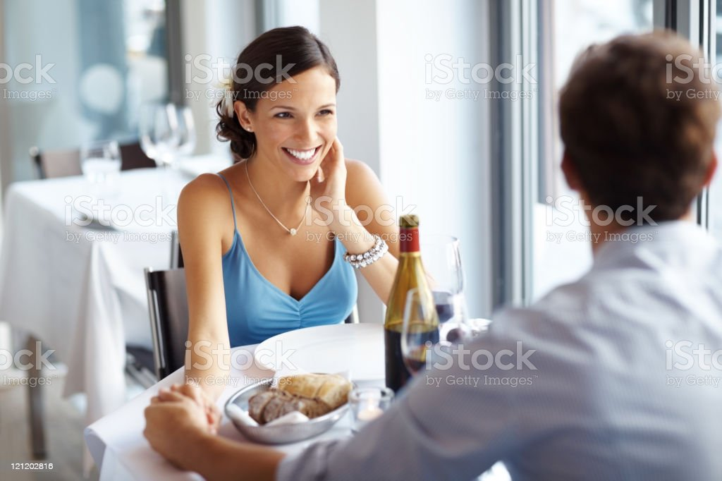Smiling young woman with her boyfriend at a cafe royalty-free stock photo