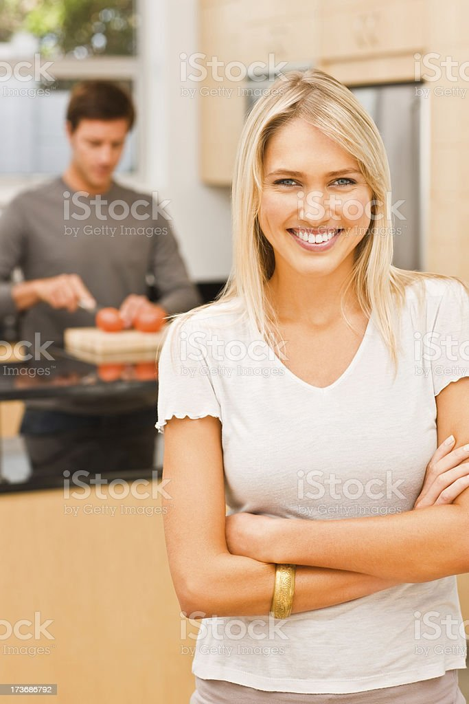 Smiling young woman with man preparing food in background royalty-free stock photo