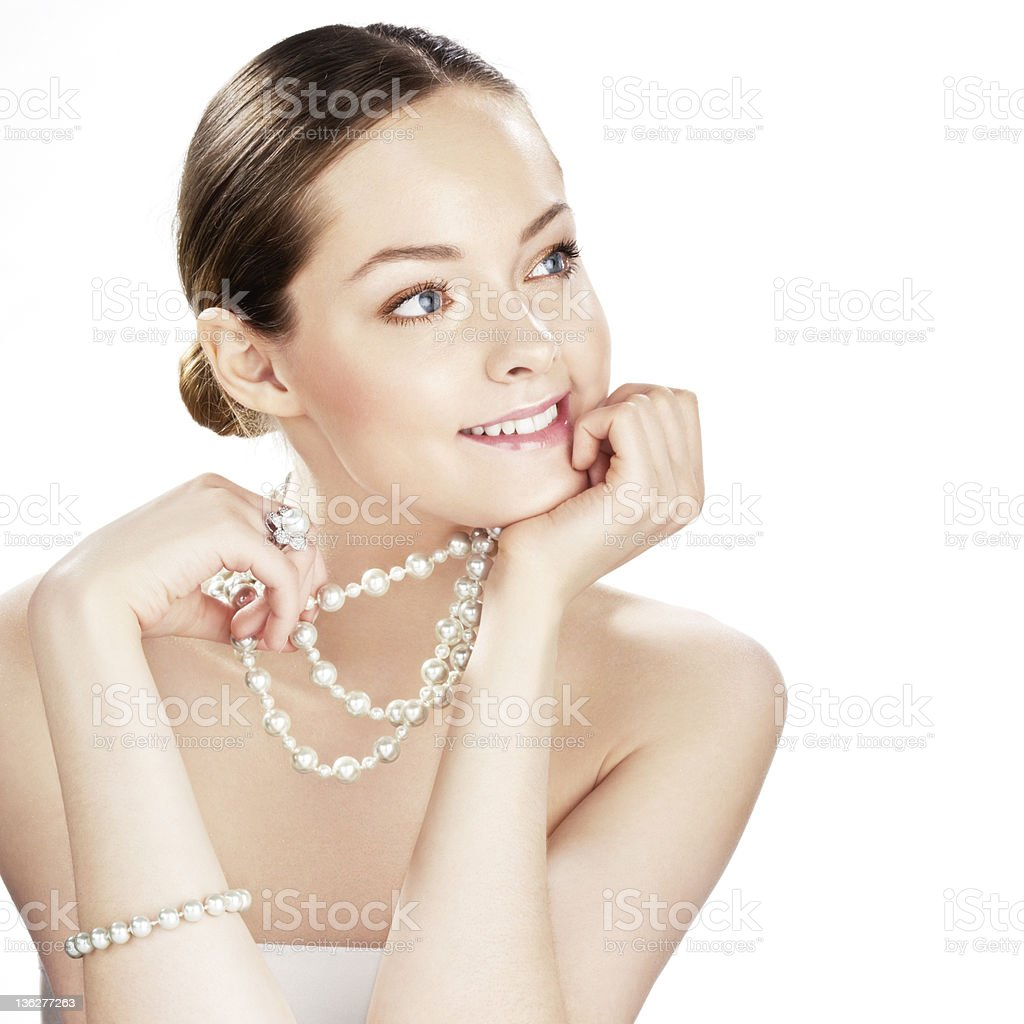 Smiling young woman with pearl jewelry holding her head stock photo