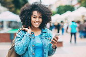Smiling young woman with smart phone