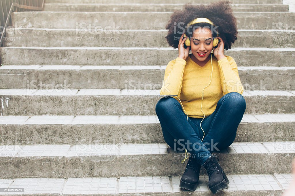 Smiling young woman with yellow headphones sitting on stairs stock photo