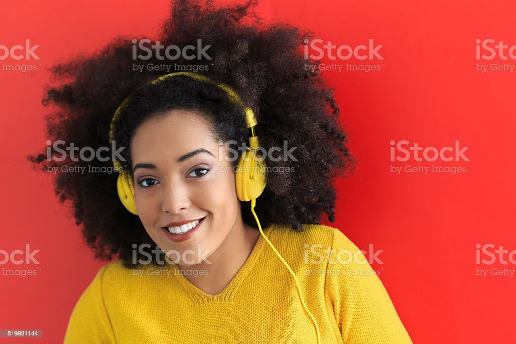 Smiling young woman with yellow headset listening music stock photo
