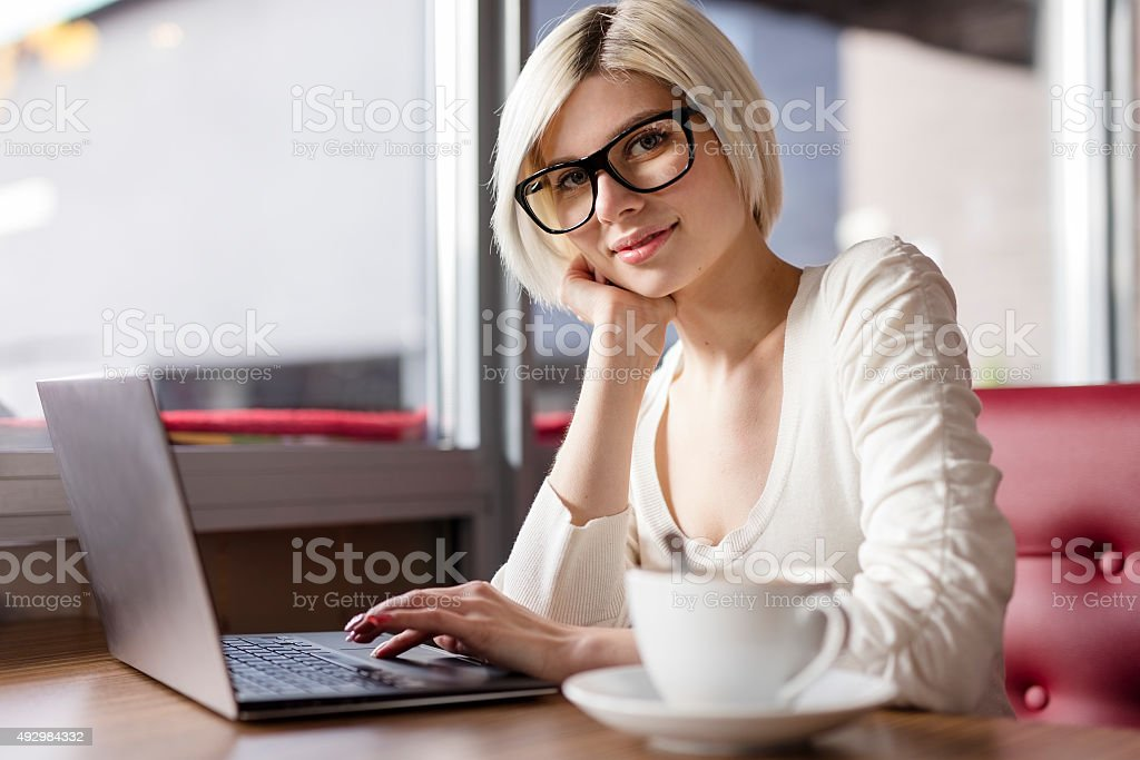 Smiling young woman working with laptop computer in cafe stock photo