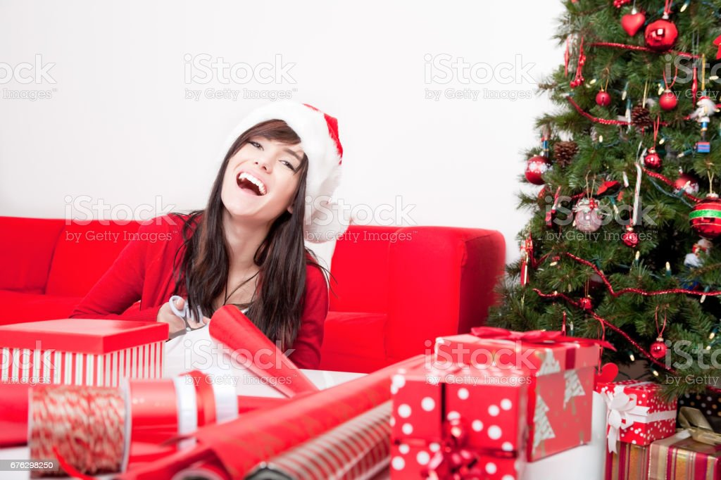 Smiling young woman wrapping christmas gifts stock photo