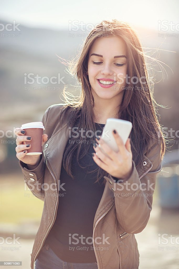 Smiling Young Women holding Coffee and Texting on Smartphone stock photo